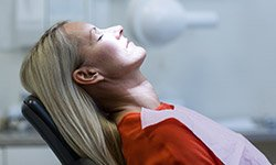 Relaxed woman with eyes closed in dental chair