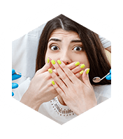 Woman in dental chair covering mouth