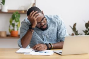 Stressed man sits in front of a laptop with head in hand